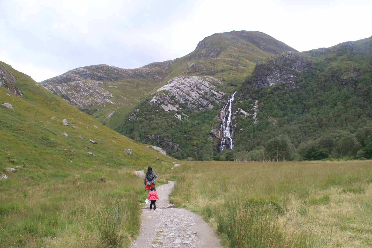Tahia and Julie getting closer to Steall Falls while simultaneously swatting (futilely) at midges with their hats