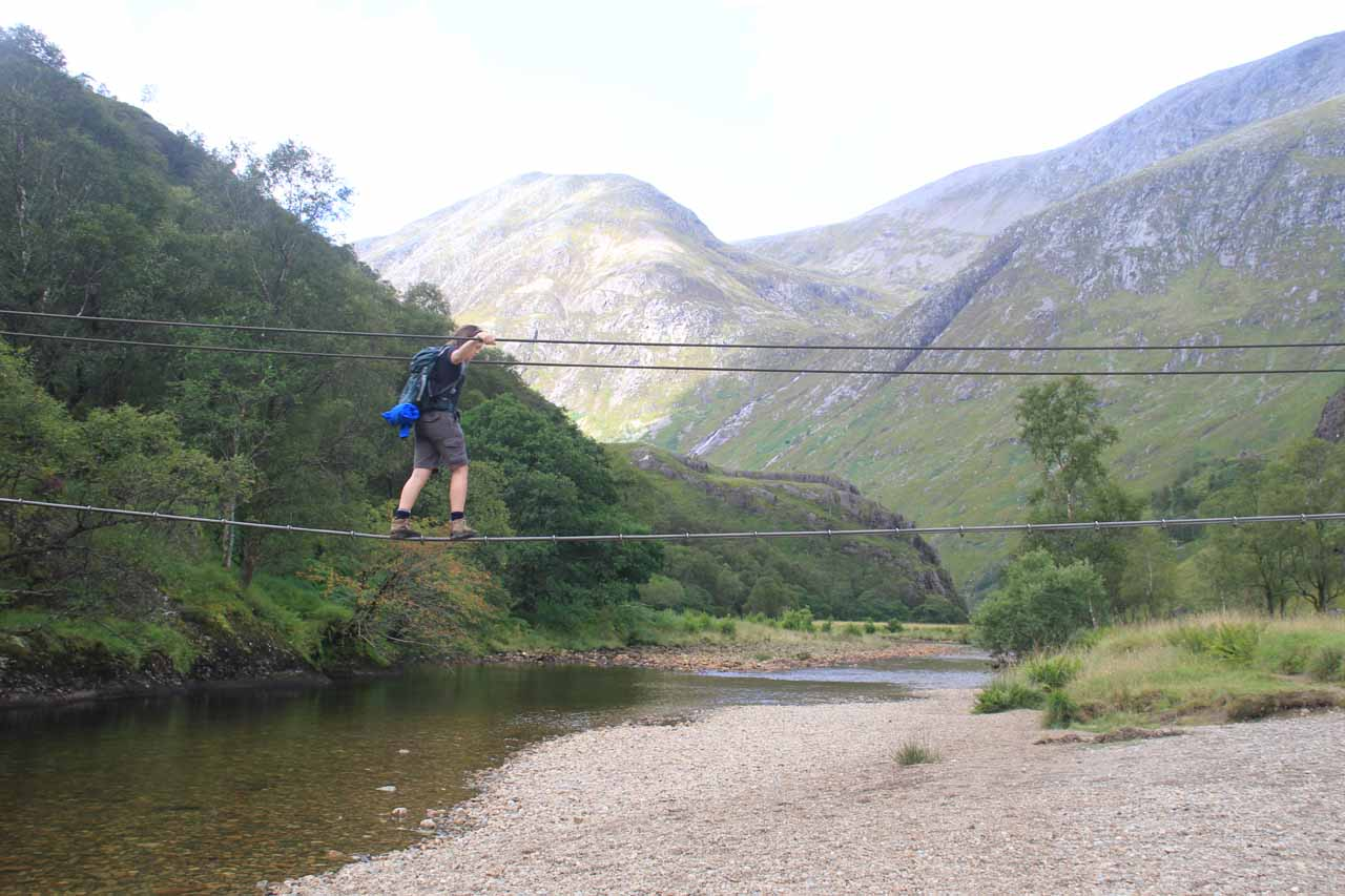 A hiker crossing the three-wire bridge