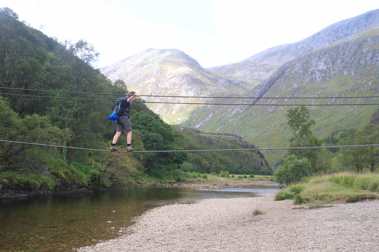 A hiker crossing the three-wire bridge