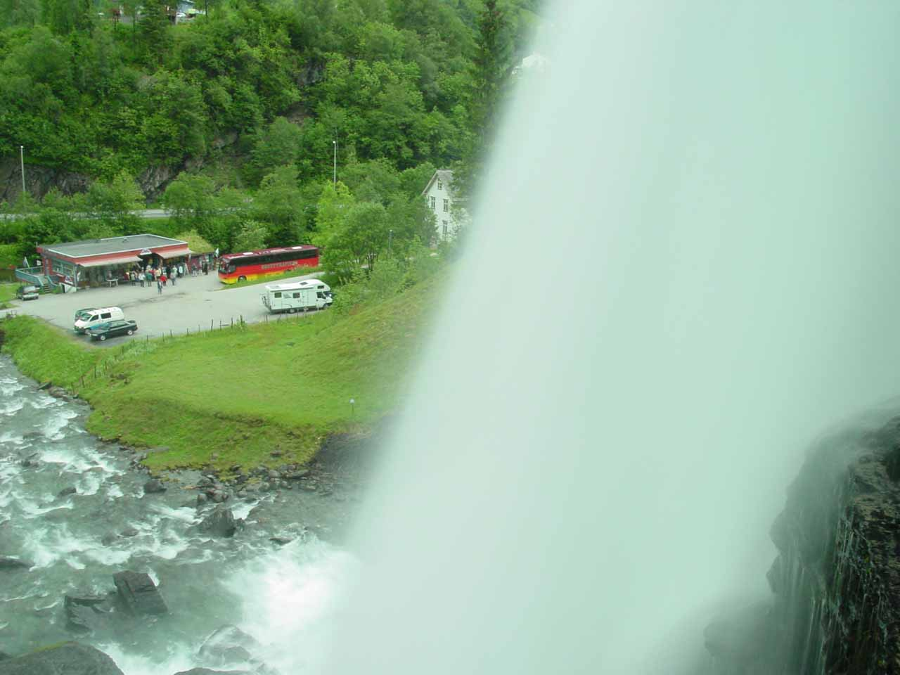Looking out from behind Steinsdalsfossen down towards the tour buses and souvenir shops