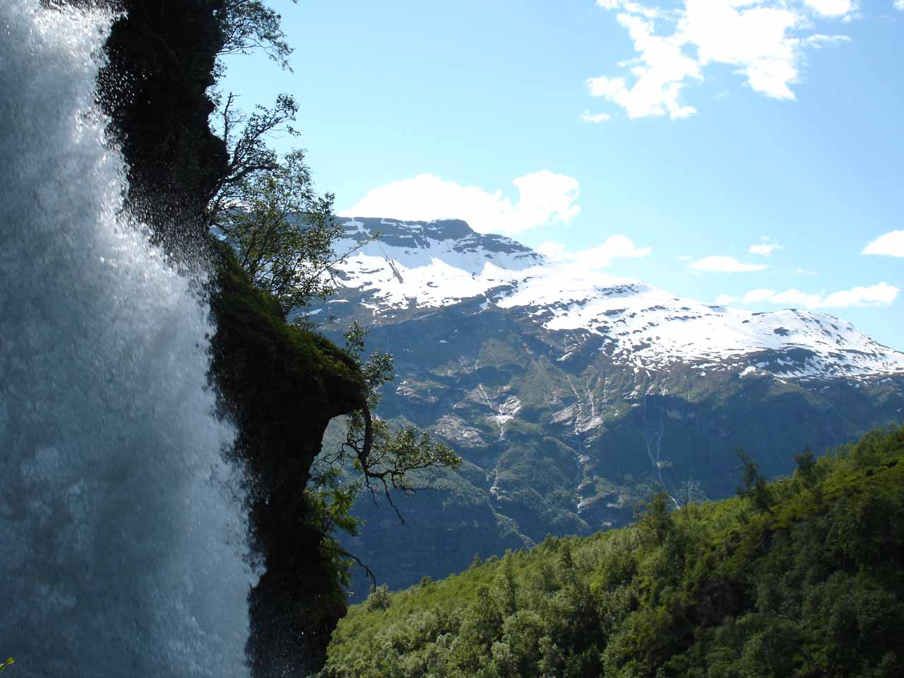 Looking out towards snowy-capped mountains from behind Storsæterfossen. Indeed, this was one of those waterfalls that we could get behind
