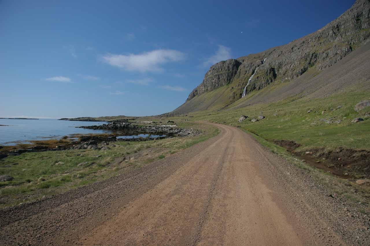 The road weaving between the Atlantic and cliffs full of waterfalls along the Strandir Coast