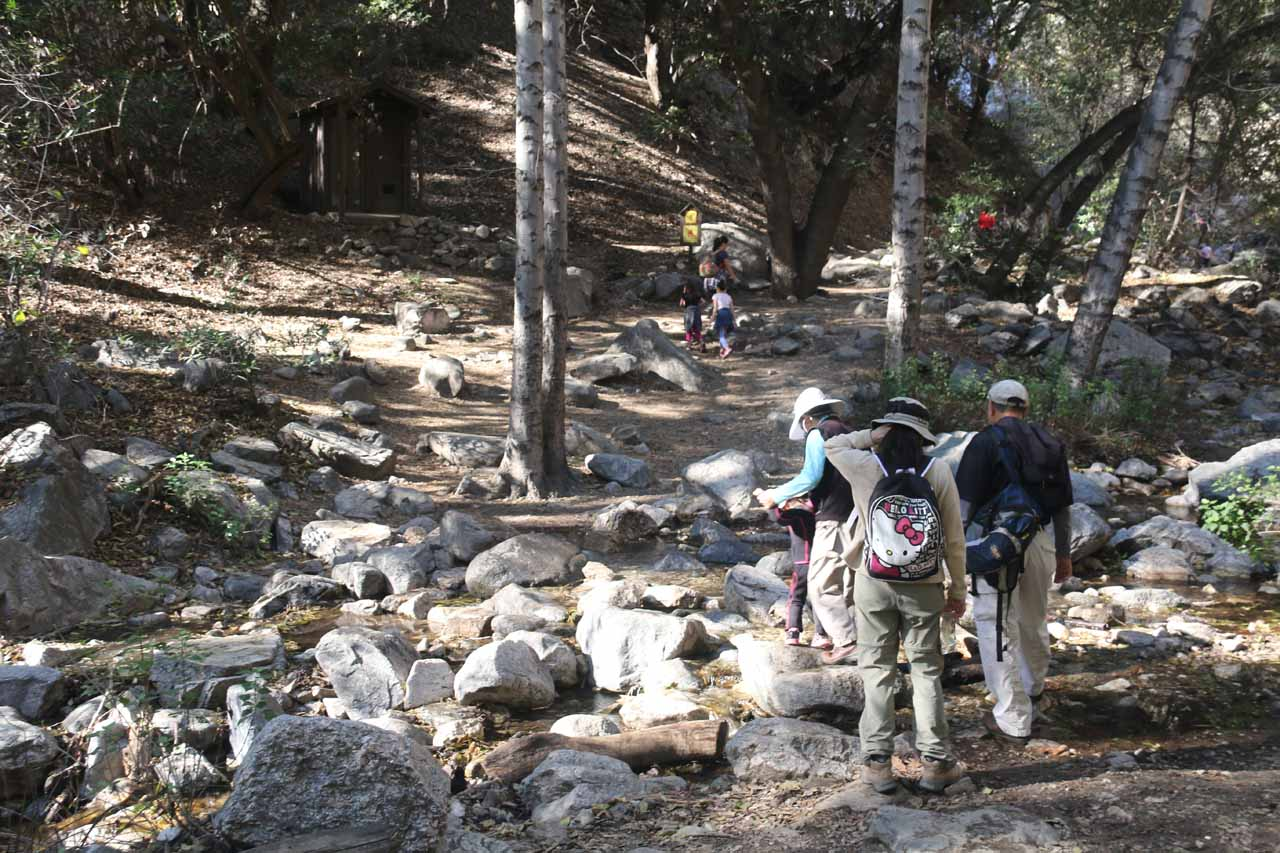 The family traversing one of the creek crossings near the base of Sturtevant Falls