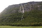 Sunndalen_058_07162019 - Contextual look back at Vinnufossen over a field and some forest at the base of the cliffs