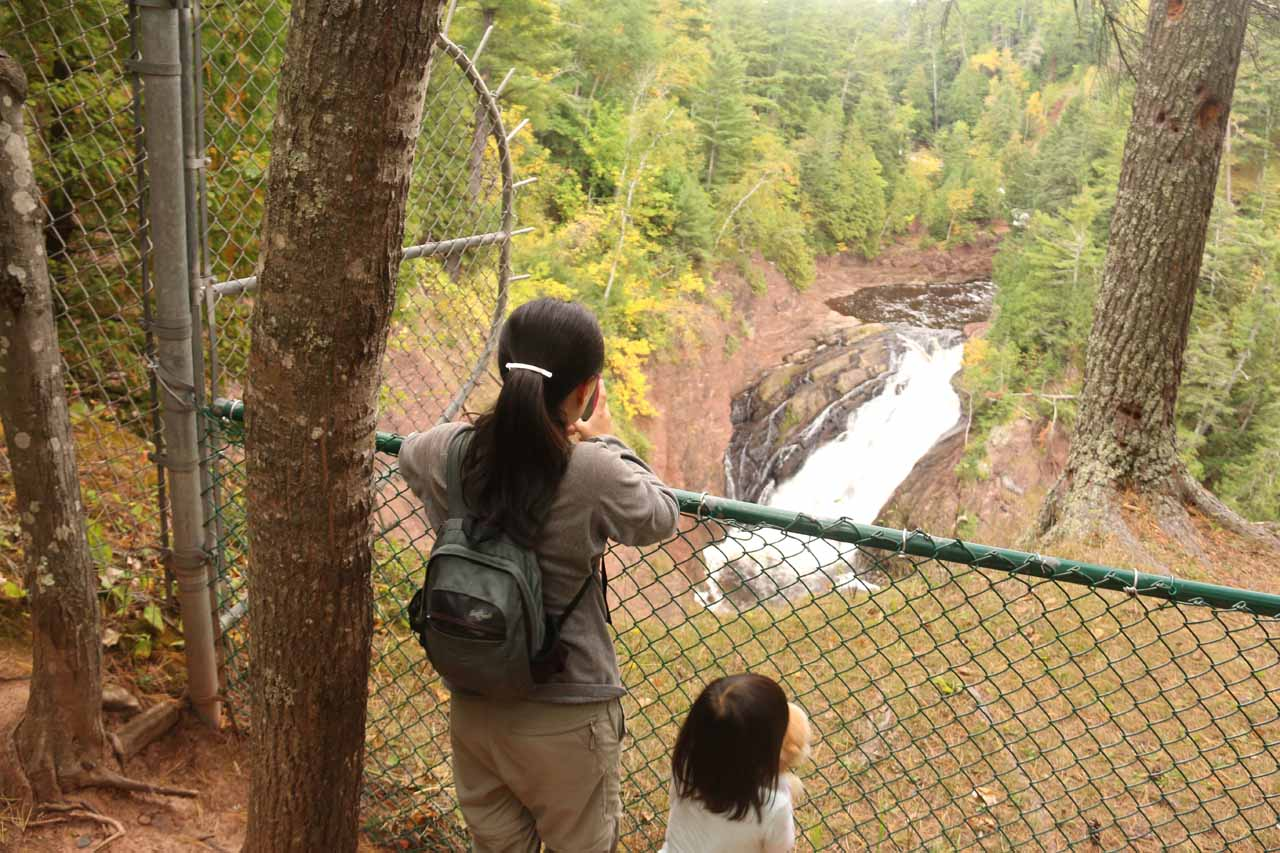 Context of Julie and Tahia checking out Superior Falls as they stood behind fencing to keep them away from the cliff edge