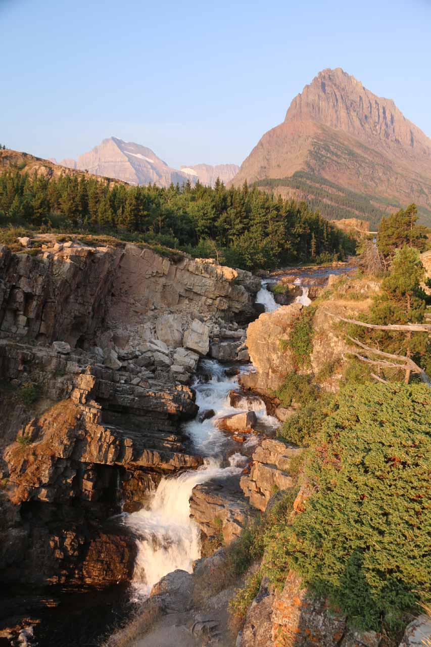 Portrait look back at Swiftcurrent Falls and Mt Grinnell from the rock outcrop seen in the early morning