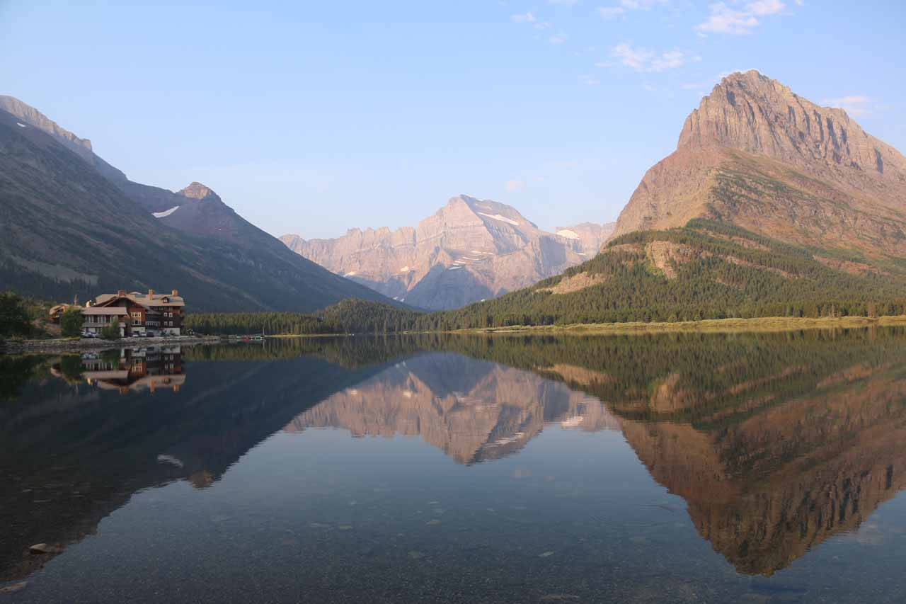 Morning view over the reflective Swiftcurrent Lake framed by the Many Glacier Hotel and Mt Grinnell as seen from near the bridge over Swiftcurrent Creek