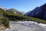 Switzer_Falls_018_12282019 - Descending the empty road towards the Lower Picnic Area at the trailhead for Switzer Falls with snow still flanking the road itself