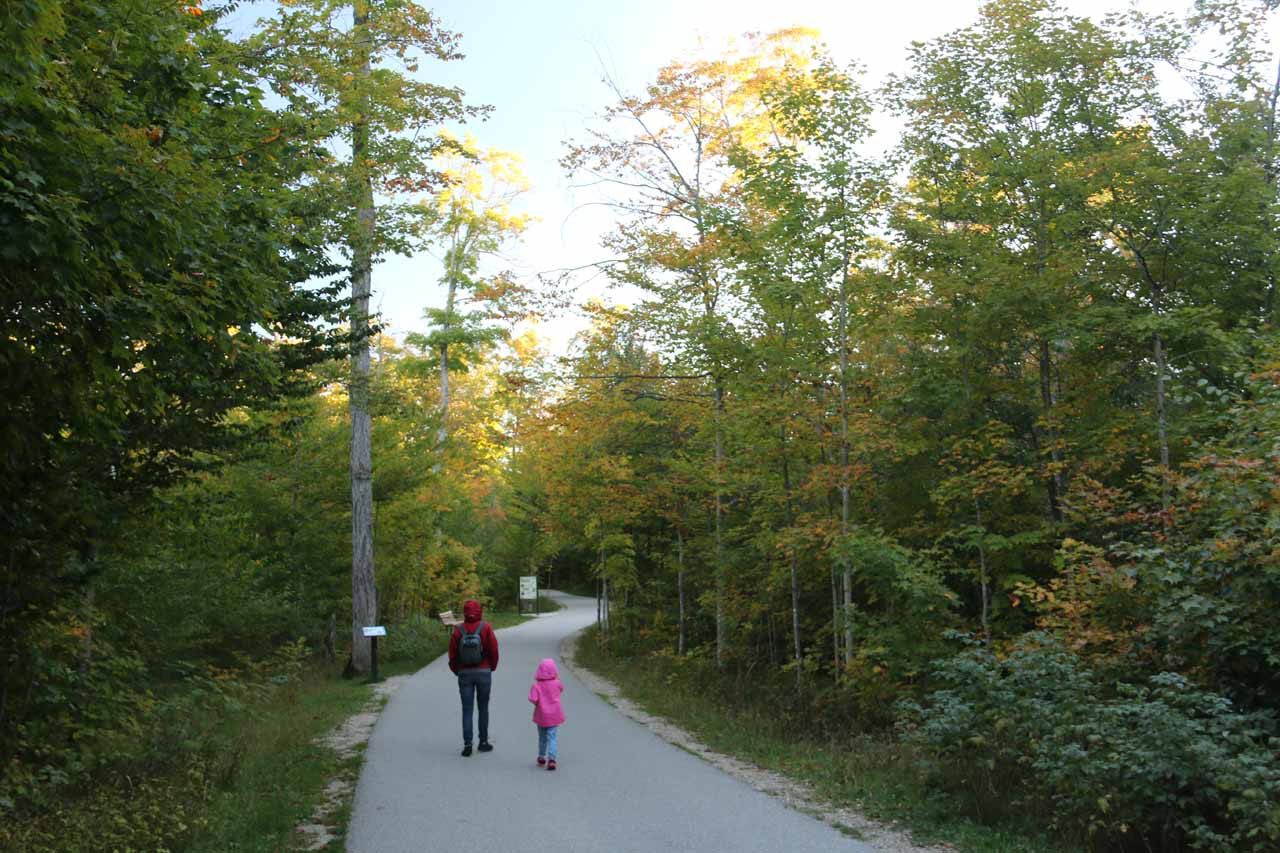 Julie and Tahia on the well-developed walkway flanked by tall trees (some of them starting to change color) and some interpretive signs