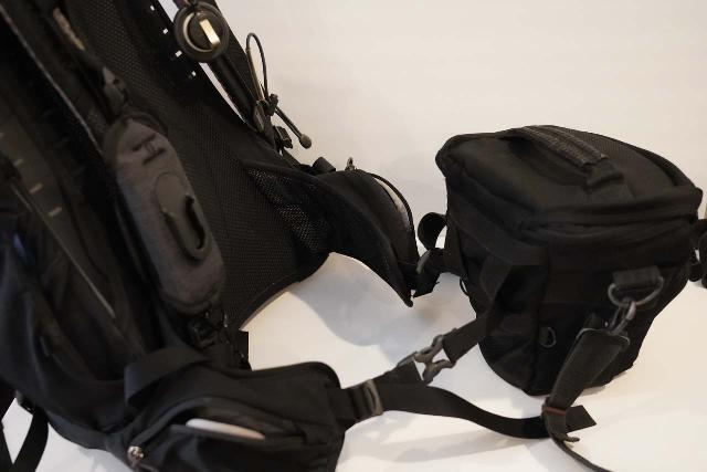After wearing my day pack and slinging the Tamrac 5627 across my body, then I'd loop the hip belt and buckle through the camera bag's hip belt loops before fastening the belt for a tight fit and letting the weight sit on my hips and legs (so the camera bag straps lightly rest on my shoulder)