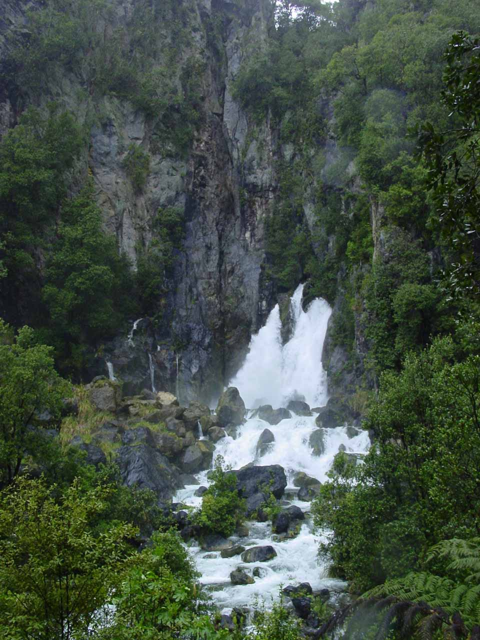 Full context of Tarawera Falls with the high cliffs towering over the gushing waterfall