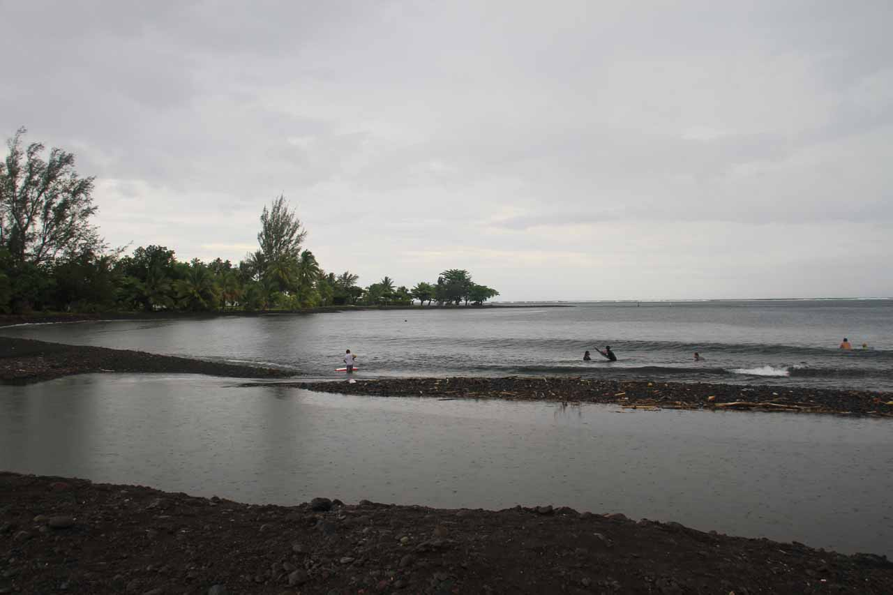 Locals catching smaller waves closer to the black-sand beach at Teahupoo