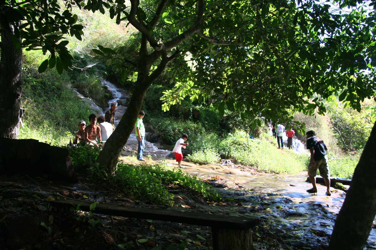 People getting wet and playing by a stream right beneath the Thararak Waterfall