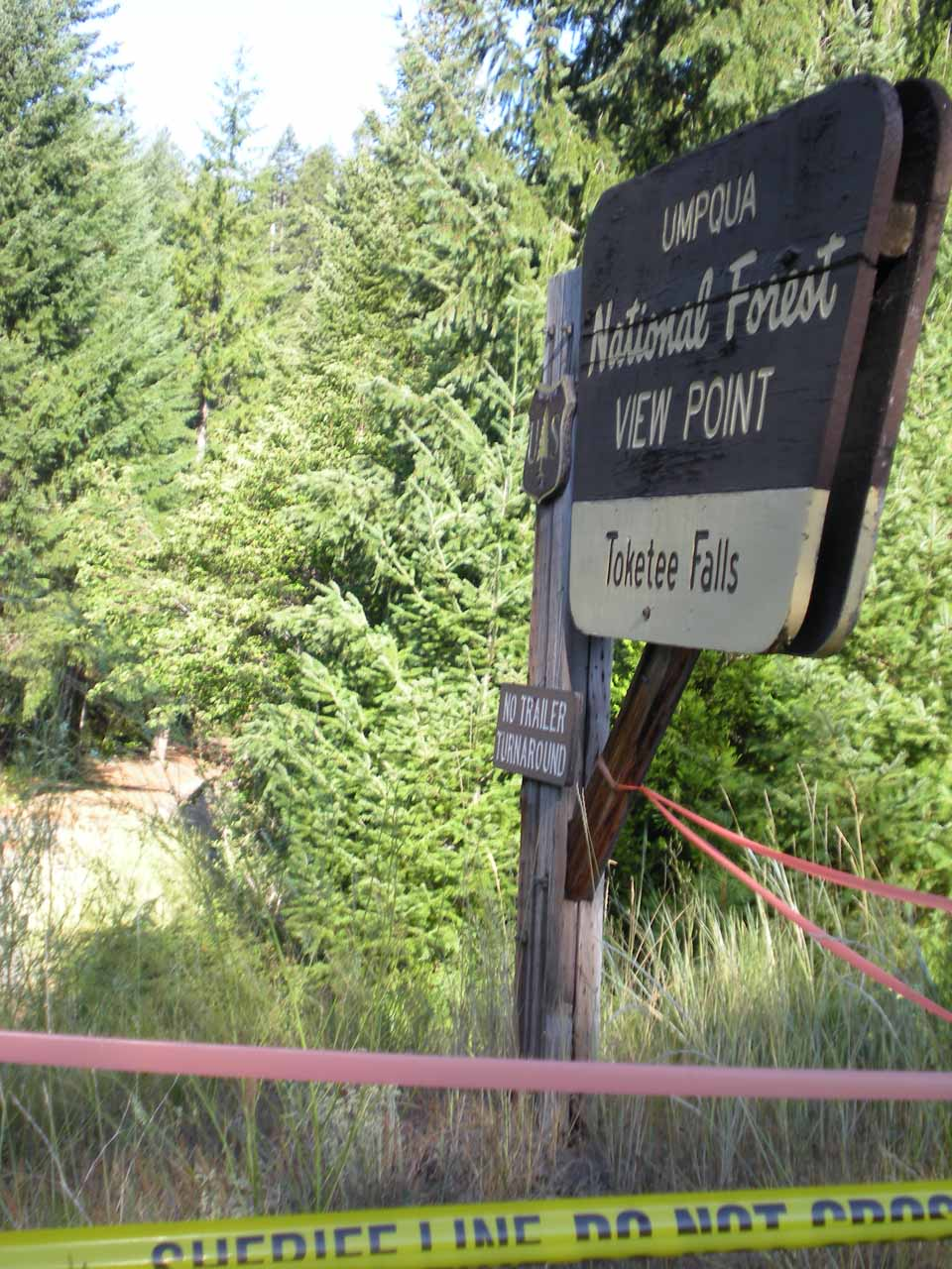 Police tape and other things strung across the trail to prevent entry