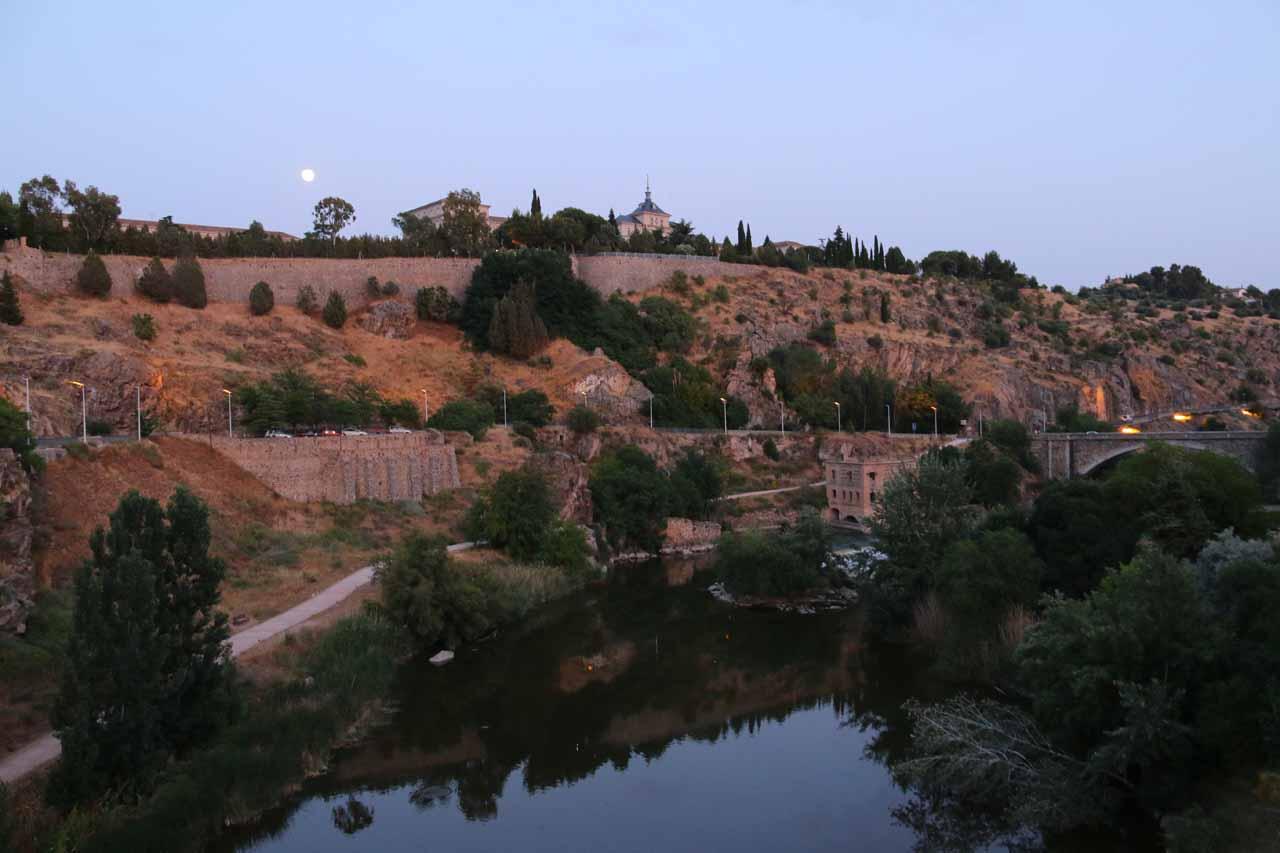 Twilight view with full moon over both the Rio Tajo and Academia de Infanteria from the Puente Nuevo de Alcantara