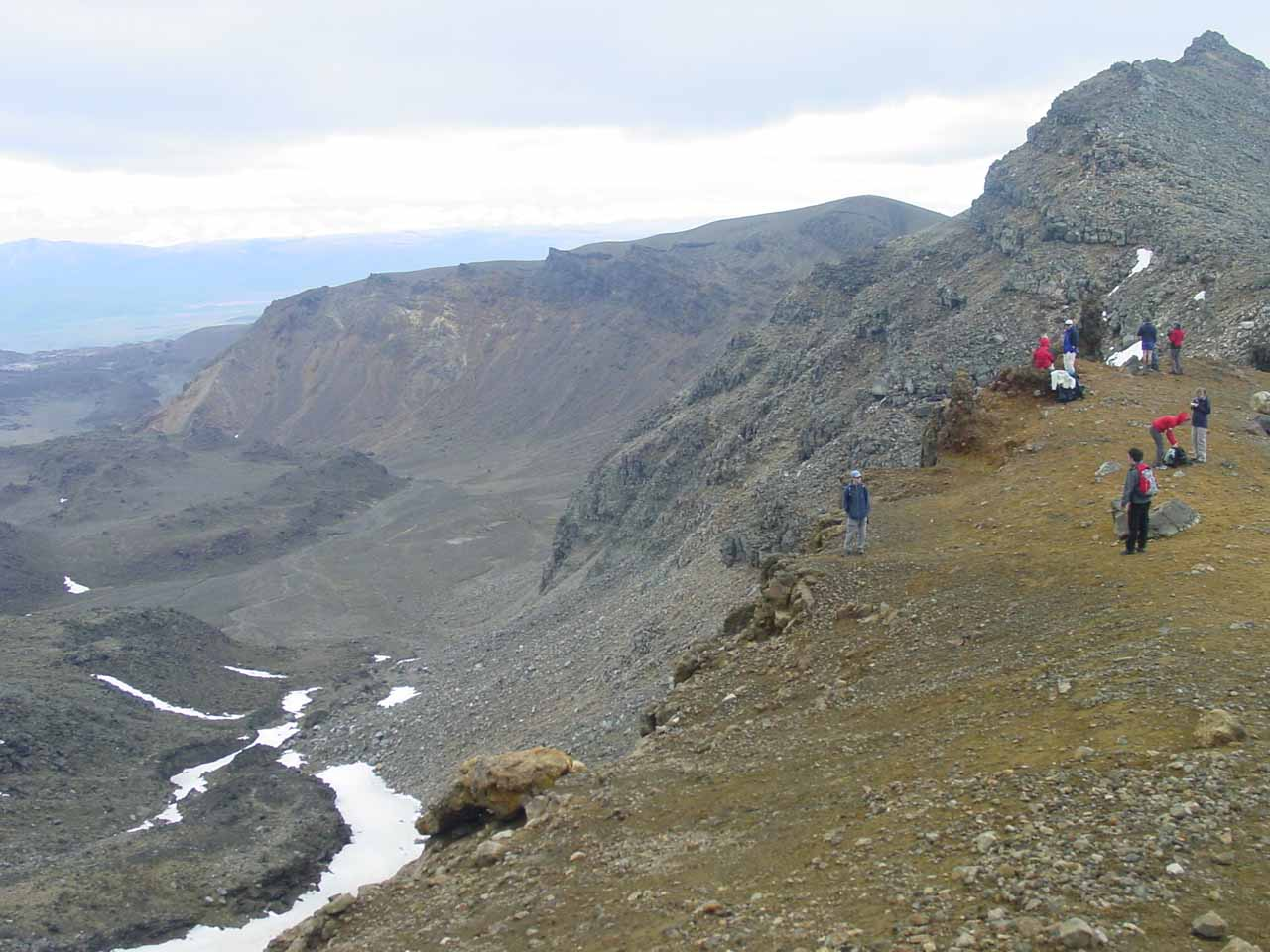 On the edge of another crater with some other people looking on along the Tongariro Crossing