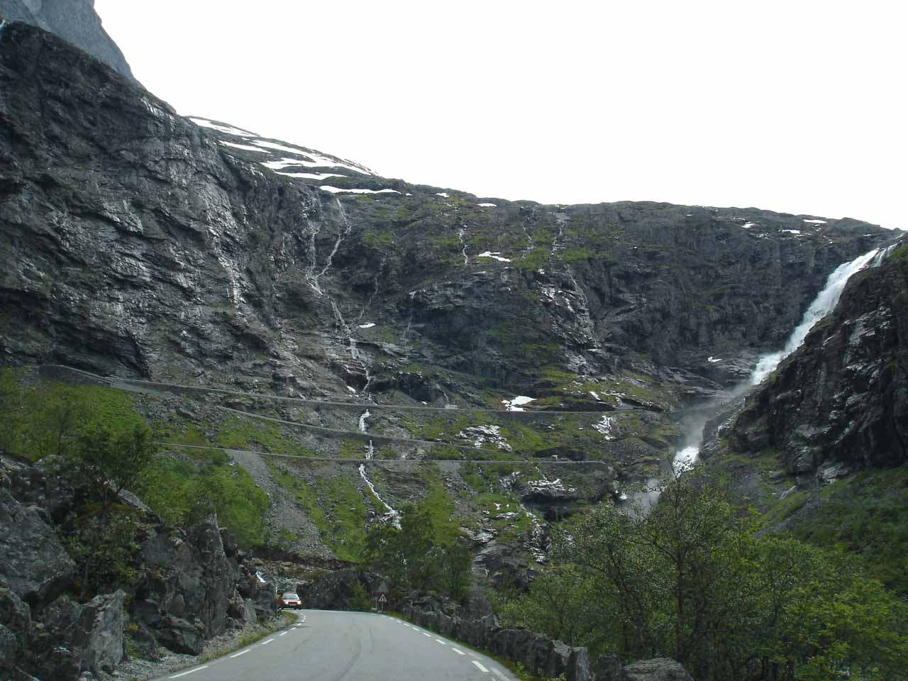 The imposing wall that Trollstigen would ascend with Stigfossen coming into view
