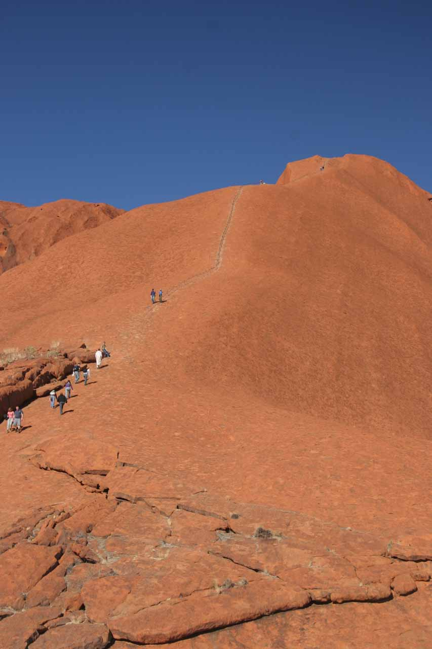 Looking at people climbing Uluru with what appeared to be trail markers making it easier to go up