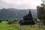 Urnes_stavkirke_062_07202019 - Panoramic view of the Urnes Stave Church with the Lustrafjorden in the background under some heavy clouds
