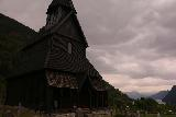 Urnes_stavkirke_146_07202019 - Context of the front of the Urnes Stave Church with hint of Lustrafjorden underneath some dark clouds