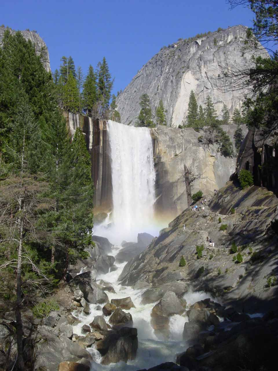 Vernal Fall and Liberty Cap with a rainbow spanning across its base from the Lady Franklin Rock next to the Mist Trail
