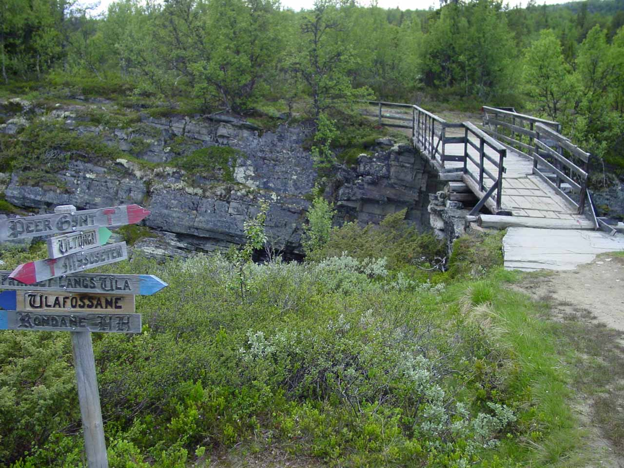 The bridge over Store Ula River with lots of signs pointing in all sorts of directions