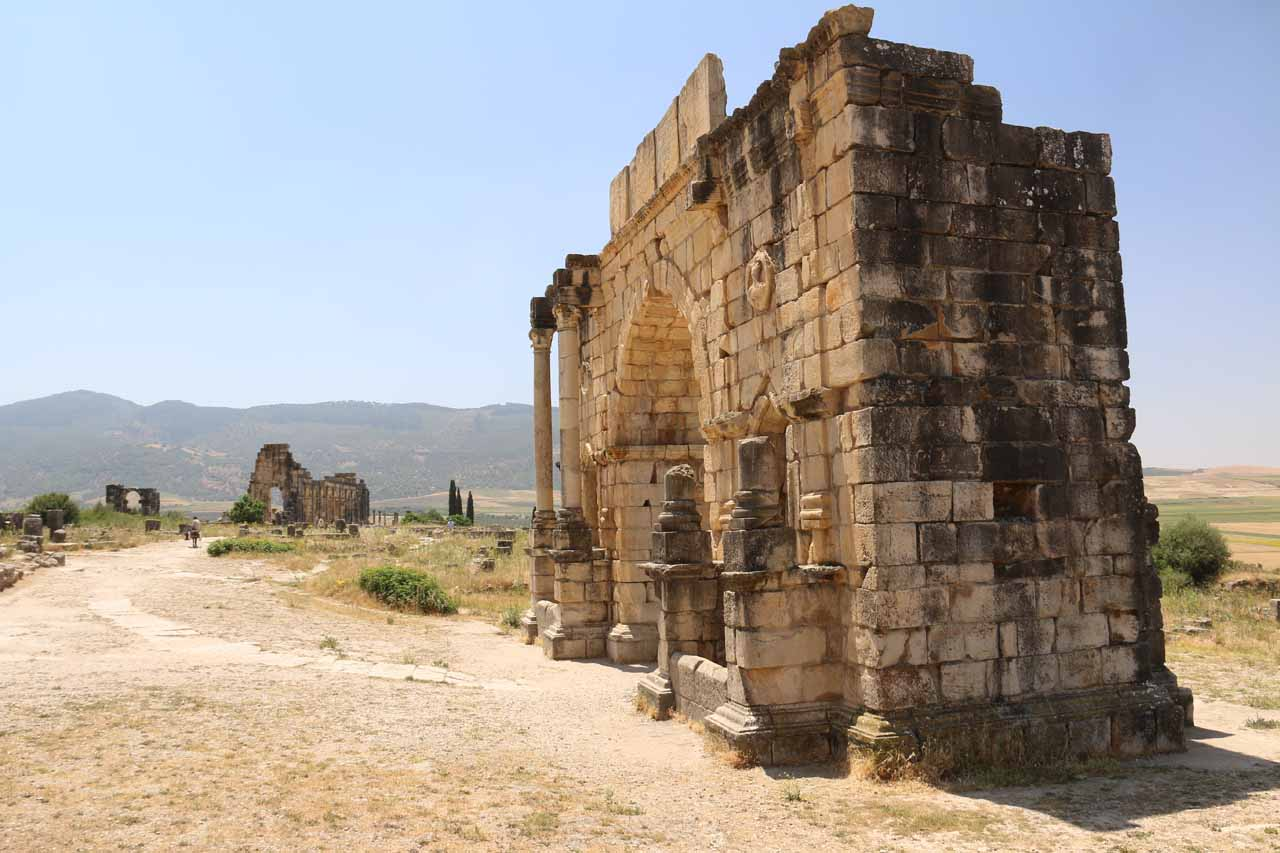 Angled look at the context of the Triumphal Arch against some other neighboring ruins in Volubilis