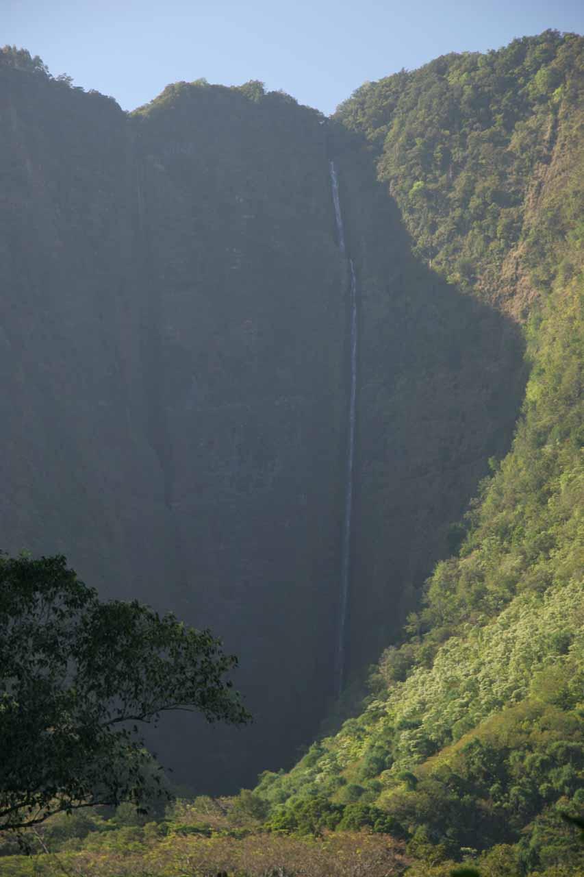 A flowing Hi'ilawe Falls in shadow