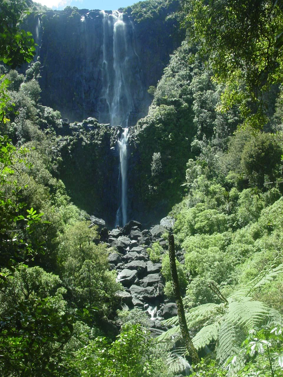A photograph taken of a waterfall under sun