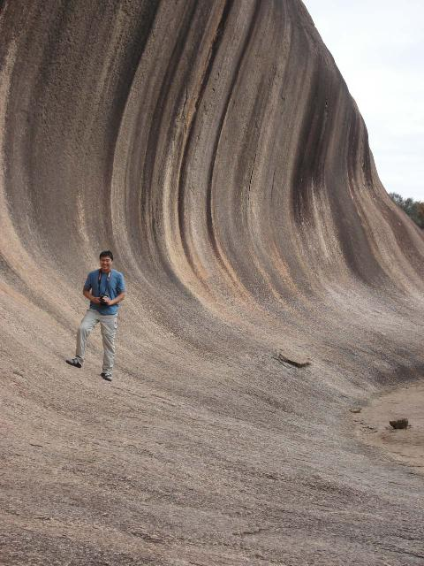 That's me carrying a Canon EOS DSLR camera with the default strap around my neck at Wave Rock in Western Australia