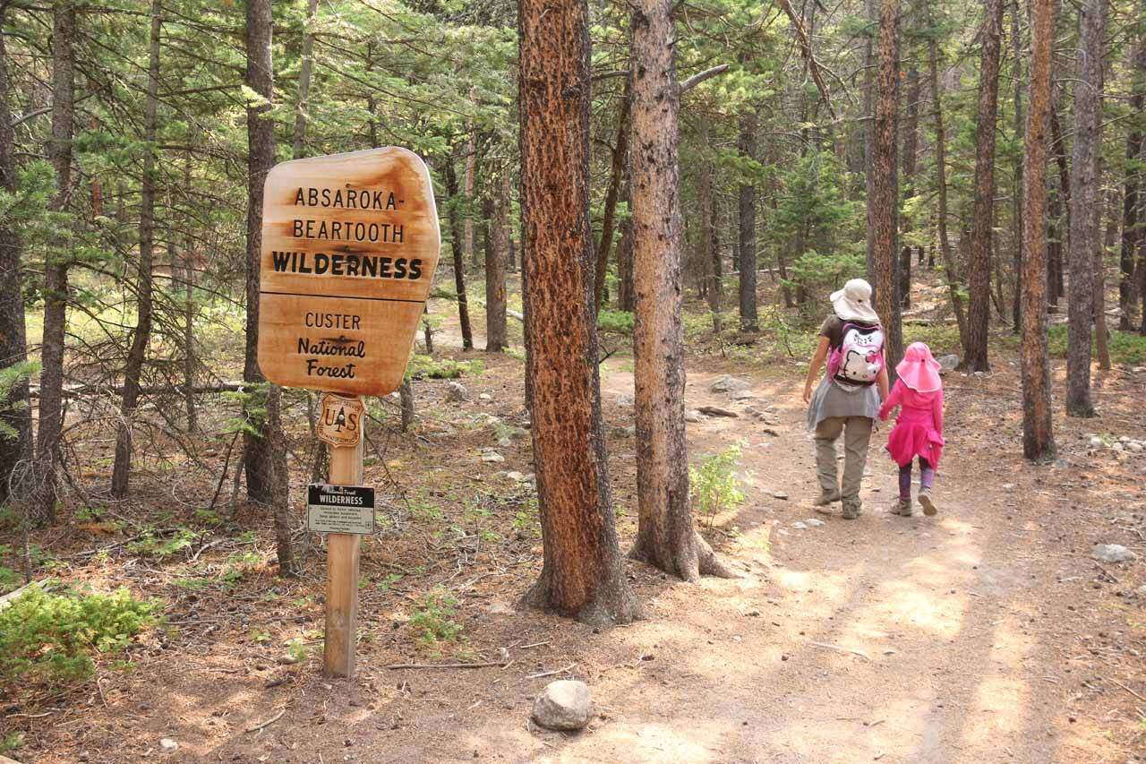Julie and Tahia hiking past the Absaroka-Beartooth Wilderness sign