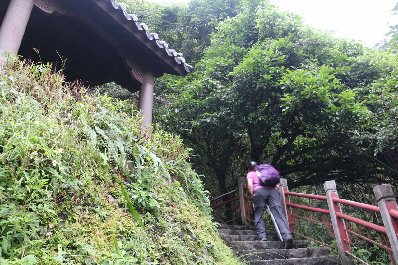 Mom walking up past a lookout shelter on the way up to the uppermost Wufengchi Waterfall