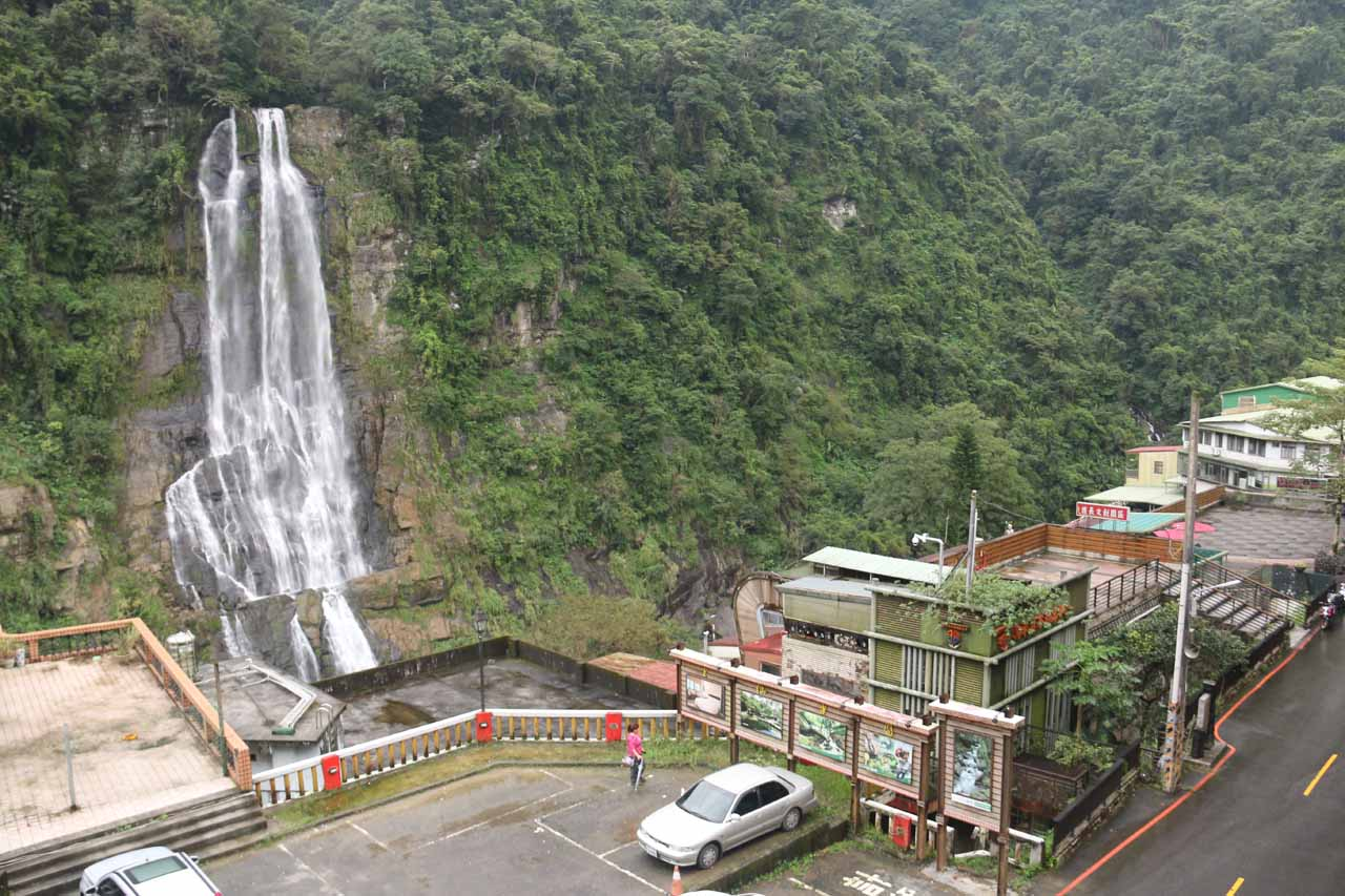 Looking down at a car park below the cable car station backed by the main drop of the Wulai Waterfall