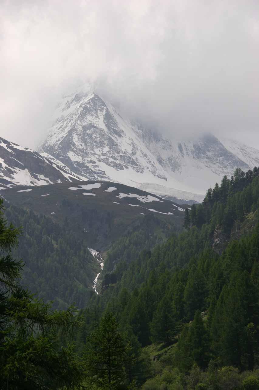A cascade tumbling beneath a cloud-covered Matterhorn